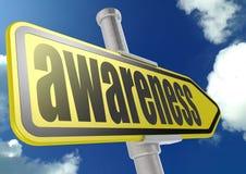 Желтый дорожный знак с словом осведомленности под голубым небом Стоковое Фото