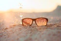 Желтый песчаный пляж sunglasseson с выплеском Стоковые Фото