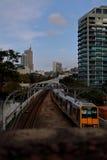 Желтый поезд приходя назад к городу с голубым небом Стоковая Фотография