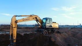 Желтый современный мощный экскаватор Hyundai выкапывает землю видеоматериал