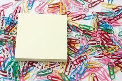 Желтый стикер напоминания на куче paperclips Стоковое Изображение