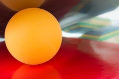 Желтый теннисный мяч расположен между 2 ракетками настольного тенниса, предпосылкой конца-вверх стоковые фотографии rf