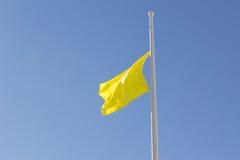 Желтый флаг на половинном рангоуте Стоковое Изображение