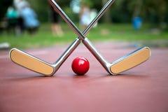 Желтый цвет пересек железные ракетки и красный шарик на суд a minigolf Стоковые Изображения