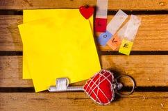 Желтый чистый лист бумаги с алфавитом влюбленности с красным ключом сердца стоковое фото