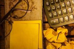 Желтый чистый лист бумаги с калькулятором с скомканной бумагой с стеклами дальше стоковые фотографии rf