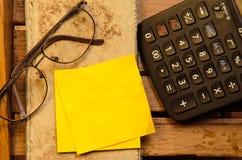 Желтый чистый лист бумаги с калькулятором с скомканной бумагой с стеклами с карандашем стоковые изображения