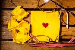 Желтый чистый лист бумаги с скомканной бумагой с 2 стеклами и меньшим красным сердцем на деревянное pettern стоковое фото rf