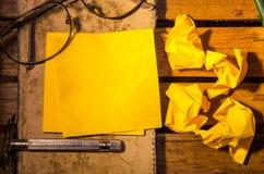 Желтый чистый лист бумаги с скомканной бумагой с стеклами с карандашем на старой книге стоковое изображение rf