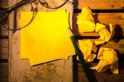 Желтый чистый лист бумаги с скомканной бумагой с стеклами с карандашем на старой книге стоковое изображение