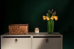 Желтый daffodil цветет при фиолетовый тюльпан зацветая в вазе с зеленой стеной Стоковые Изображения