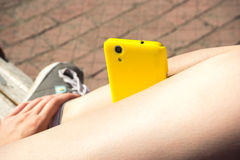 Желтый smartphone на ногах девушки Стоковые Изображения