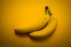 2 желтых банана на желтой предпосылке Стоковая Фотография RF