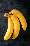 3 желтых банана на темном несенном подносе Стоковое фото RF