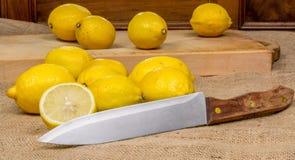 13 желтых лимона на деревянной доске и холсте и ноже на переднем плане Стоковые Изображения