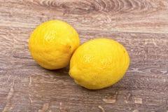 2 желтых лимона на деревянной предпосылке Стоковое Изображение