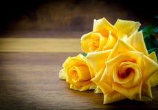 3 желтых розы на деревянной предпосылке Стоковое Изображение