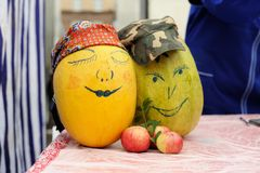 2 желтых сквоша с покрашенными сторонами женщины и человека с сулоем Стоковое Фото