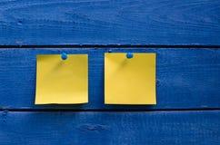 2 желтых стикера на голубой деревянной стене Стоковое Фото