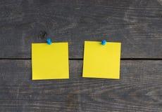 2 желтых стикеры и штыря на деревянной стене Стоковое Изображение