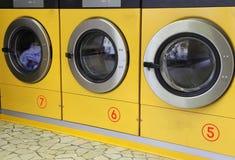 3 желтых стиральной машины в автоматических прачечных Стоковое Изображение