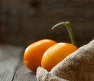 2 желтых томата на деревянном столе с дерюгой Стоковая Фотография