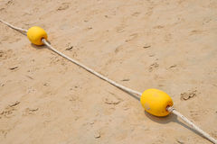 2 желтых томбуя отметки на пляже песка Стоковые Фото