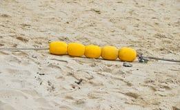 4 желтых томбуя отметки на пляже песка Стоковая Фотография RF