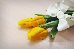 3 желтых тюльпана на деревянной предпосылке Стоковое Изображение