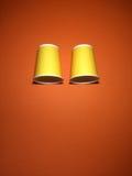 2 желтых устранимых чашки на оранжевой предпосылке Стоковые Фото