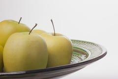 3 желтых яблока в керамическом баке на белой предпосылке Стоковые Фото