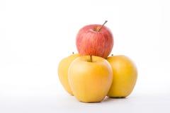 3 желтых яблока и красный цвет на белой предпосылке Стоковое Изображение