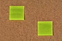 Желт-зеленые стикеры чистого листа бумаги на старом волосистом картоне Стоковая Фотография RF