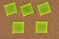 Желт-зеленые стикеры чистого листа бумаги на старом волосистом картоне Стоковое Изображение