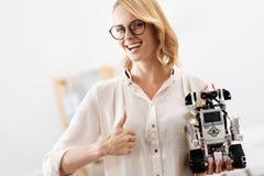 Живая женщина демонстрируя цифровой маленький робот внутри помещения стоковое фото rf
