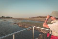 Живая природа туриста наблюдая бинокулярным пока на круизе шлюпки на граница реке Chobe, Намибии Ботсване, Африка Национальный па Стоковые Фото