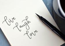ЖИВЕТ ВЛЮБЛЕННОСТЬ СМЕХА рук-lettered в блокноте стоковая фотография rf