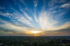 Живой заход солнца над ландшафтом джунглей с валунами и деревьями Стоковые Изображения RF