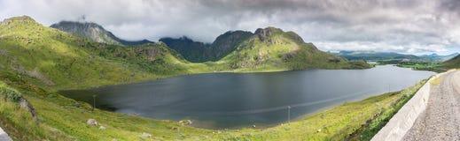 Живописные зеленые холмы и озеро вдоль дороги, Lofoten, Норвегии Стоковое Изображение
