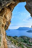 Живописный взгляд острова, молодой человек взбираясь утес Desti перемещения Стоковые Фотографии RF