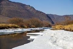 Живописный взгляд реки в снеге и льда в зиме между величественными горами Стоковая Фотография RF