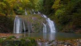 Живописный водопад этапа с малым lakelet в лесе осени Кавказа 4K видеоматериал