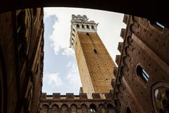 Живописный нижний взгляд Torre del Mangia (башни Mangia) изнутри двора Palazzo Publico внутреннего в Сиене, Тоскане, Италии стоковые фотографии rf