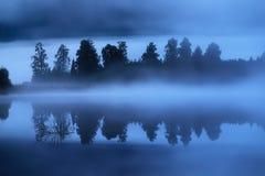 Живописный пейзаж восхода солнца на озере с туманными деревьями отраженными в воде r стоковые изображения