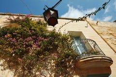 Живописный фасад с голубой дверью и красочная фиолетовая бугинвилия цветут внутри старого укрепленного города Mdina, Мальты malt стоковые изображения rf