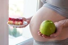 Живот беременной женщины держа плиту с старьем и здоровой едой Выбор концепции диеты во время беременности Стоковые Изображения RF