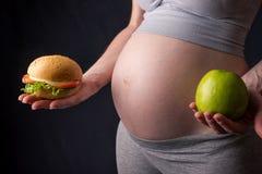 Живот беременной женщины держа плиту с старьем и здоровой едой Выбор концепции диеты во время беременности Стоковое Изображение