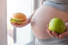 Живот беременной женщины держа плиту с старьем и здоровой едой Выбор концепции диеты во время беременности Стоковое Изображение RF