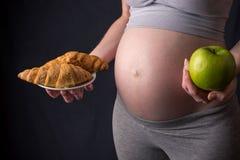 Живот беременной женщины держа плиту с старьем и здоровой едой Выбор концепции диеты во время беременности Стоковое фото RF