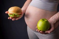 Живот беременной женщины держа плиту с старьем и здоровой едой Выбор концепции диеты во время беременности Стоковое Фото